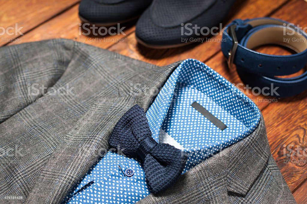 Men's suit, belt and footwear on a wooden background stock photo