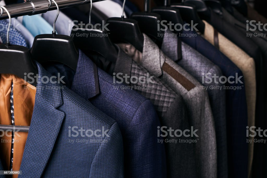 Mens suits on hangers in different colors stock photo