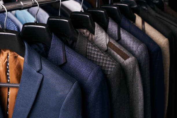 mens suits on hangers in different colors - menswear stock photos and pictures
