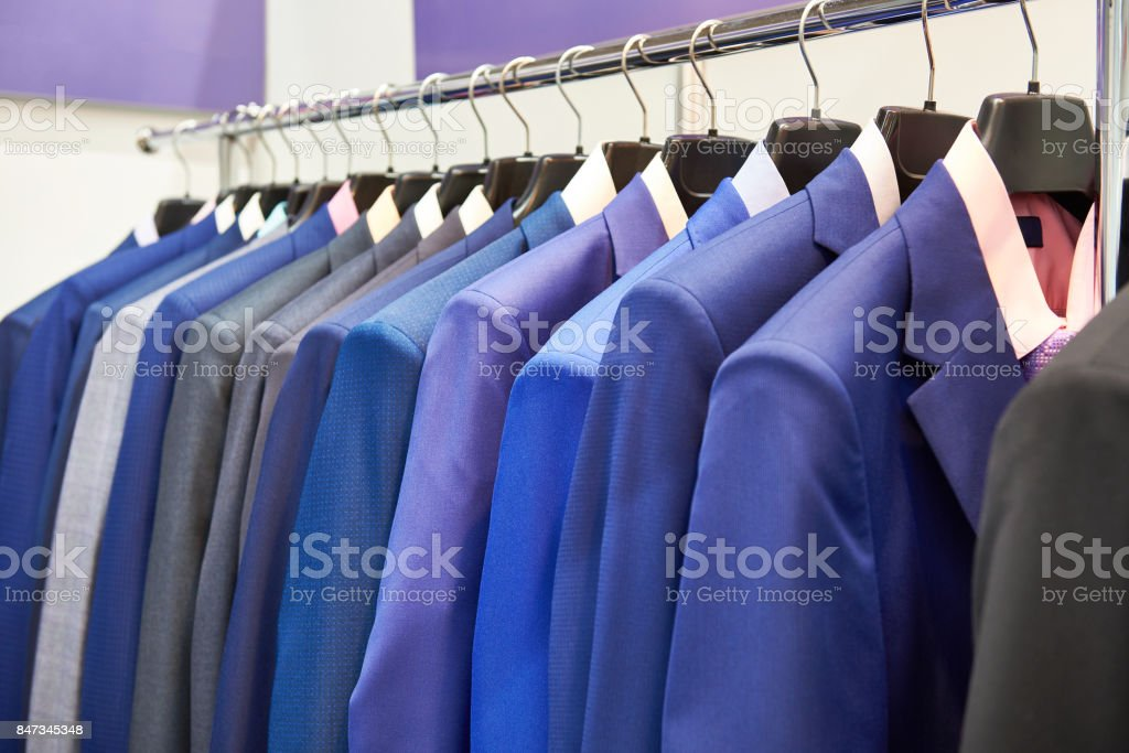 Men's suits with shirts in clothing store stock photo
