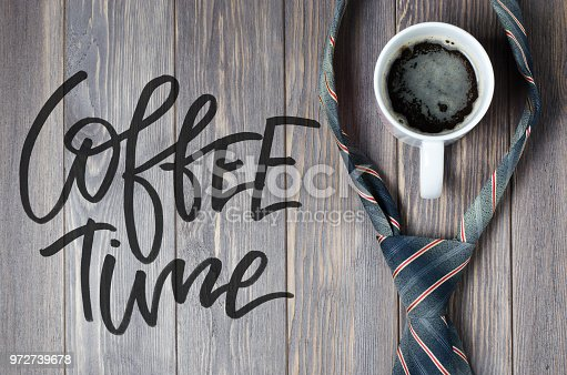 Men's tie and coffee in a white Cup on wooden background. Handwritten text - Coffee time. Flat top view