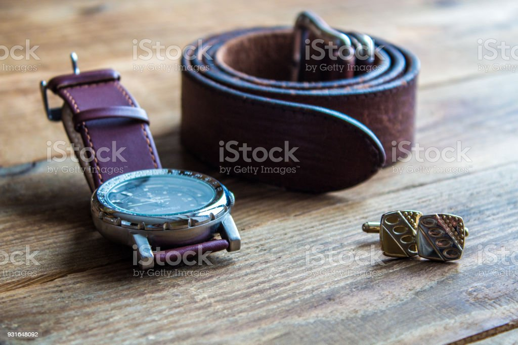 mens watches and belt and cufflincs on wooden background stock photo