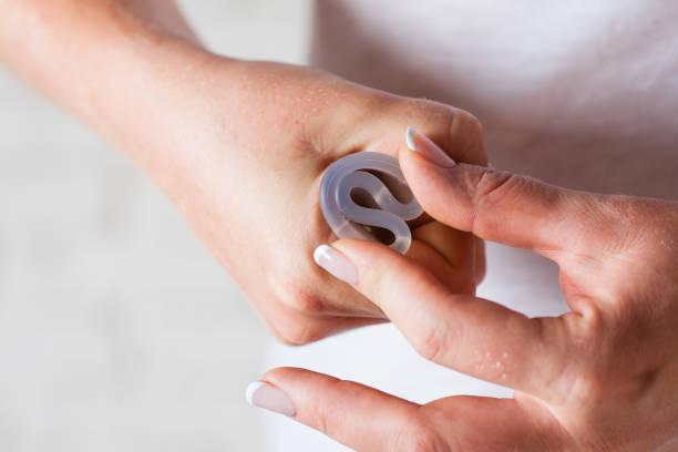 menstrual cup in female hands - coppa mestruale foto e immagini stock