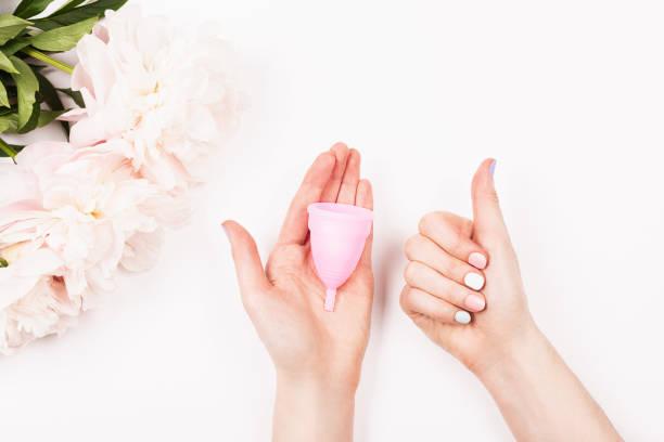 menstrual cup in woman hands. - coppa mestruale foto e immagini stock