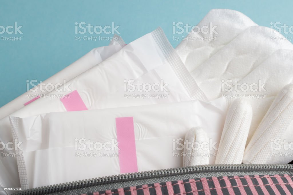 Menstrual tampons and pads in cosmetic bag. Menstruation cycle. Hygiene and protection stock photo