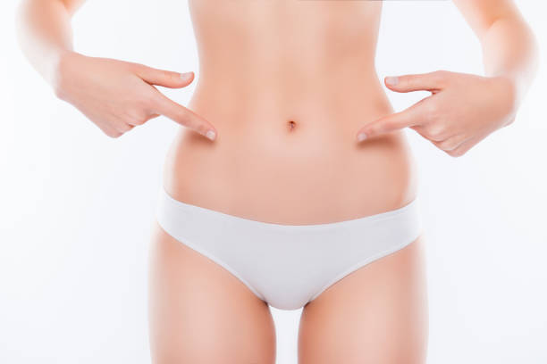 menstruation ovulation depilation epilation laser liposuction sport weight loss concept. cropped close up photo of skinny woman's ideal belly demonstrating with fingers isolated on white background - stomach stock pictures, royalty-free photos & images