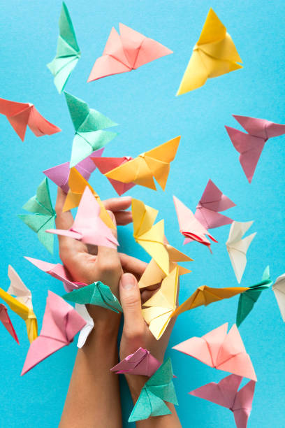 mental health concept. colorful paper butterflies flying and sitting on woman's hands. harmony emotion. origami. paper cut style. - mulher deixar ir imagens e fotografias de stock