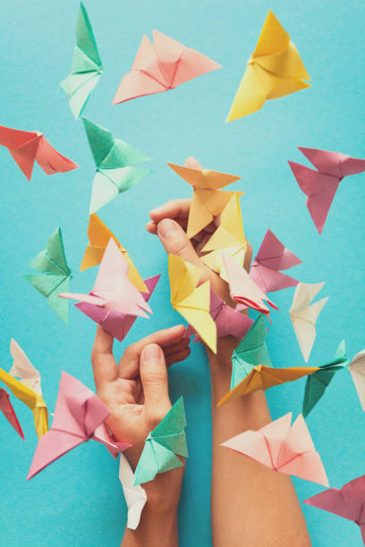 mental health concept. colorful paper butterflies flying and sitting on woman's hands. harmony emotion. origami. paper cut style. toned - mulher deixar ir imagens e fotografias de stock