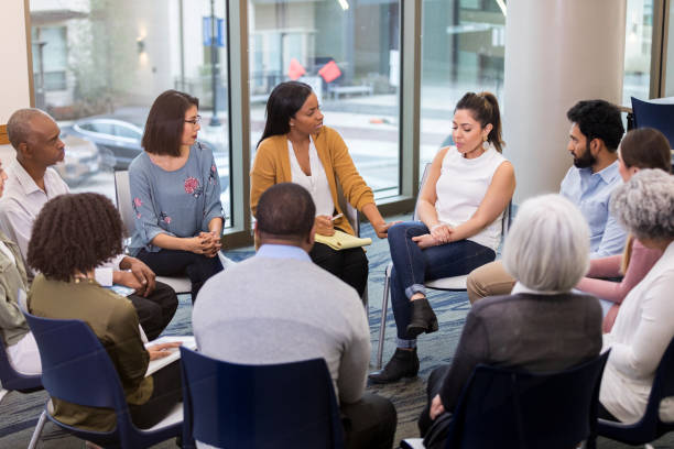Mental health professional comforts woman Upset mid adult woman discusses a difficult issue during a support group meeting. A caring mental health professional comforts and speaks encouraging words to the woman. group therapy stock pictures, royalty-free photos & images