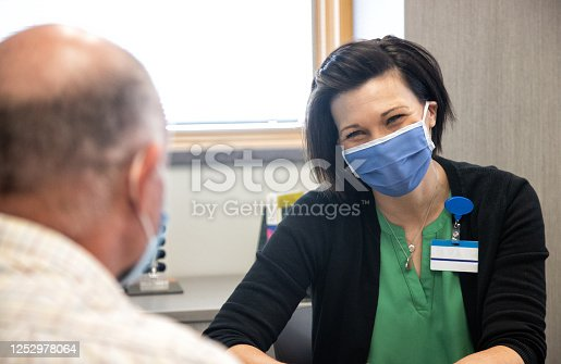 A Mental Health Professional in Her Forties Wearing a Face Mask Talks with a Masked White Male in His Sixties while Sitting at a Table in a Medical Clinic
