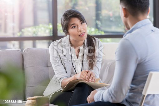 While sitting in a comfortable waiting room, female doctor listens to her patient about mental health problems. Doctor is on a sofa, wearing a lanyard and holding a clipboard.