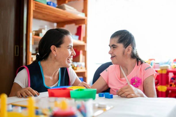 Mental Health Professional playing with Down Syndrome woman Mental Health Professional playing with Down Syndrome woman at School learning difficulty stock pictures, royalty-free photos & images