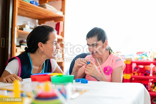 Mental Health Professional playing with Down Syndrome woman at School
