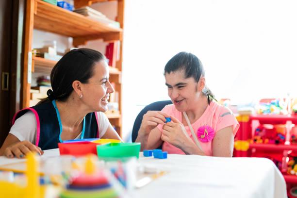 Mental Health Professional spielt mit Down-Syndrom-Frau – Foto