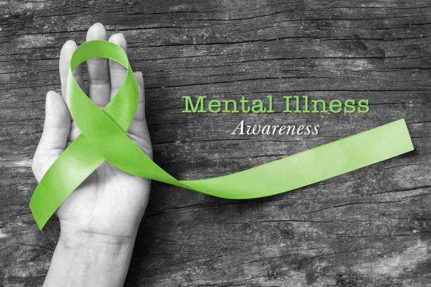 text zum sensibilisierungstext für psychische erkrankungen mit der farbe lime green, die auf der hand auf dem holzhintergrund im alten alter hilft (clipping-pfad) - psychisches problem stock-fotos und bilder