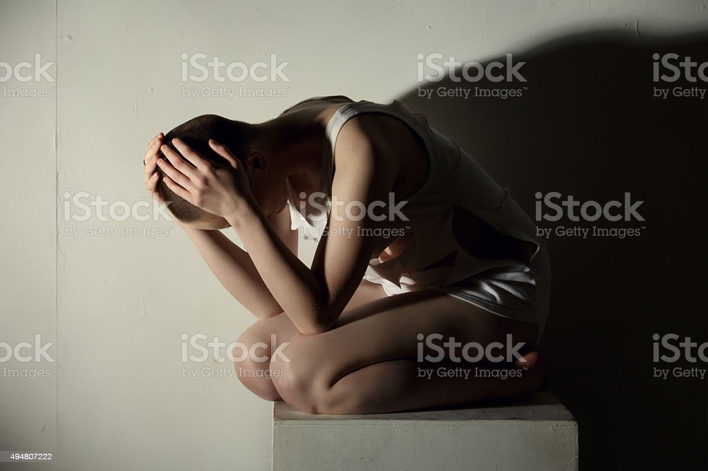Mental illness. Shot of thin girl holding her head stock photo