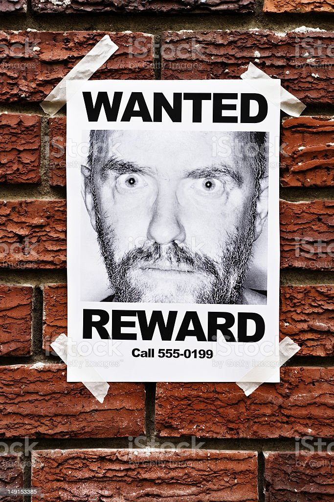 Mental patient or criminal? Wanted poster on brick wall stock photo