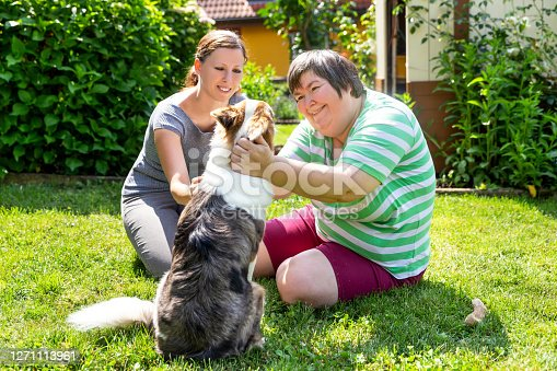 istock mentally disabled woman with a second woman and a companion dog, concept learning by animal assisted living 1271113961