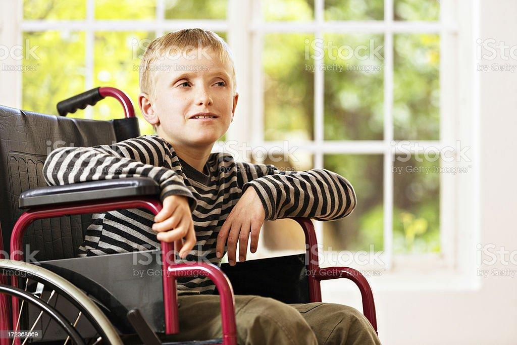 Mentally handicapped little boy in wheelchair leans forward royalty-free stock photo