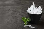 istock Menthol crystals and mint leaves on grey background. Space for text 1312607973