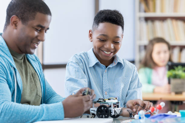 mentor and male student working together on a robot - middle school teacher stock pictures, royalty-free photos & images