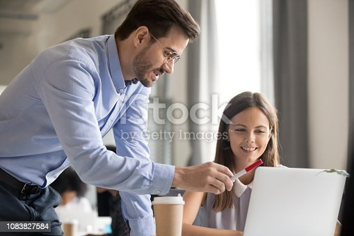 istock Mentor explaining task to smiling female employee 1083827584