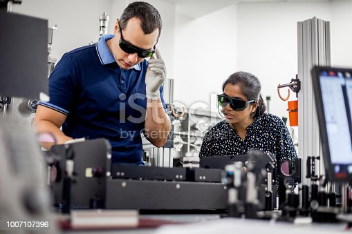 Mentor Explaining to a Student How to Use Powerful High Frequency Laser for New Materials Research.