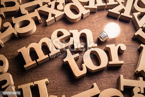 Mentor word in scattered wood letters with glowing white light bulb