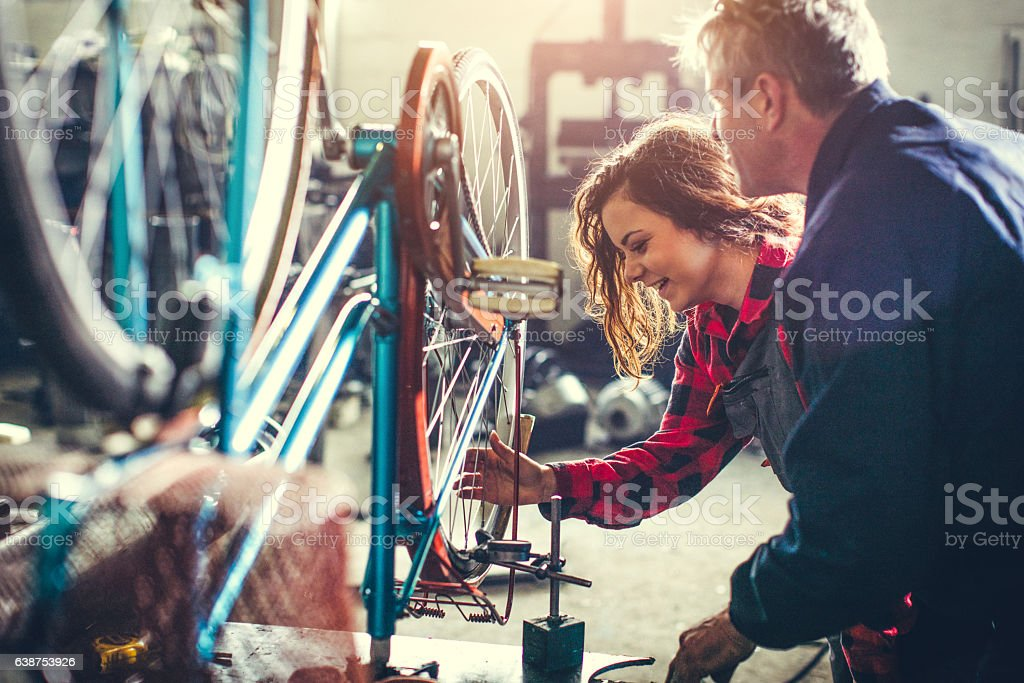 Mentor showing her worker how to do repair... stock photo