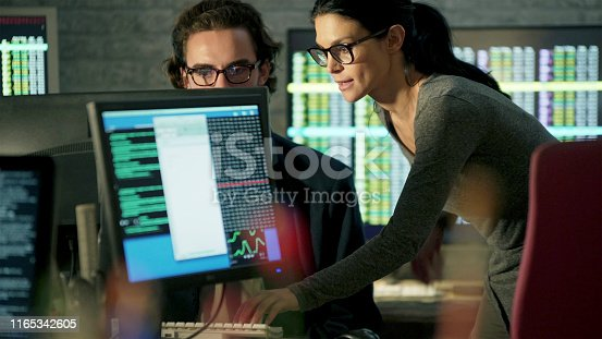 Stock photo of a good looking, mature, Hispanic woman teaching a younger man how to do an aspect of computer work. They are surrounded by computer displays showing changing numbers, stock market data etc.