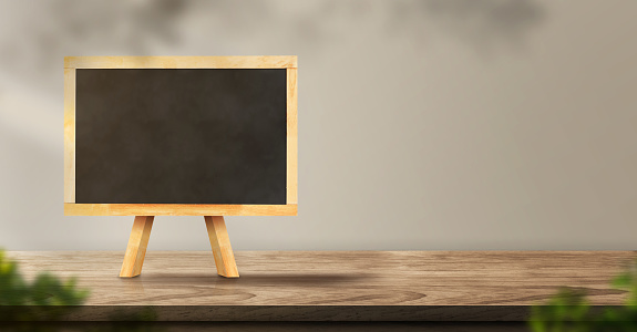 593305530 istock photo menu blackboard on wood table backgorund with sunlight window create leaf shadow on wall with blur indoor green plant foreground.panoramic banner mockup for display of product,warm tone lights 1224092214