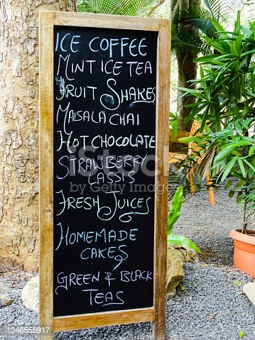 Menu Board outside a cafe, displaying name of food items for sale and a cycle parked near the board at Auroville