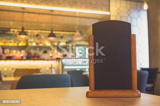 istock Menu frame standing on wood table in Bar restaurant cafe. space for text 906408082