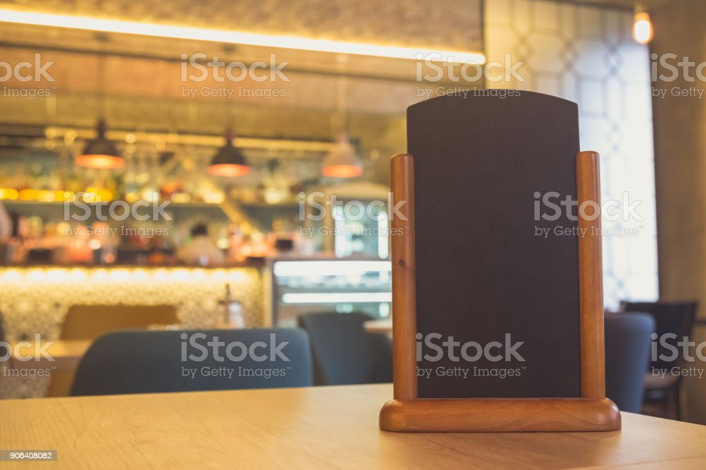 Menu frame standing on wood table in Bar restaurant cafe. space for text stock photo