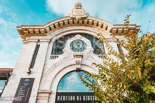 November 9th, 2019 – Lisbon, Portugal: Mercado da Ribeira at Cais do Sodré is hosting the Time Out Market as viewed from the outside of the building on a sunny day in November 2019.The Lisbon market has around 36 restaurants and kiosks selling regional specialties, such as Azeitão sheep's cheese, Alentejo ham, custard tarts from Manteigaria, shellfish and grilled fish, wines and chocolates.