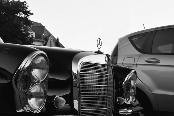 Mercedes Benz logo on a black vintage car. Mercedes-Benz is a German automobile producer. The brand is used for luxury automobiles, buses, coaches and trucks. Black white filter. stock photo