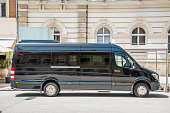istock Mercedes Benz sprinter black luxury shuttle bus van parked on the street 976657988