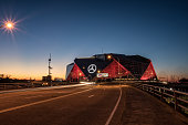 Atlanta, USA - February 2018: Cars drive by the Mercedes Benz Stadium illuminated at twilight.