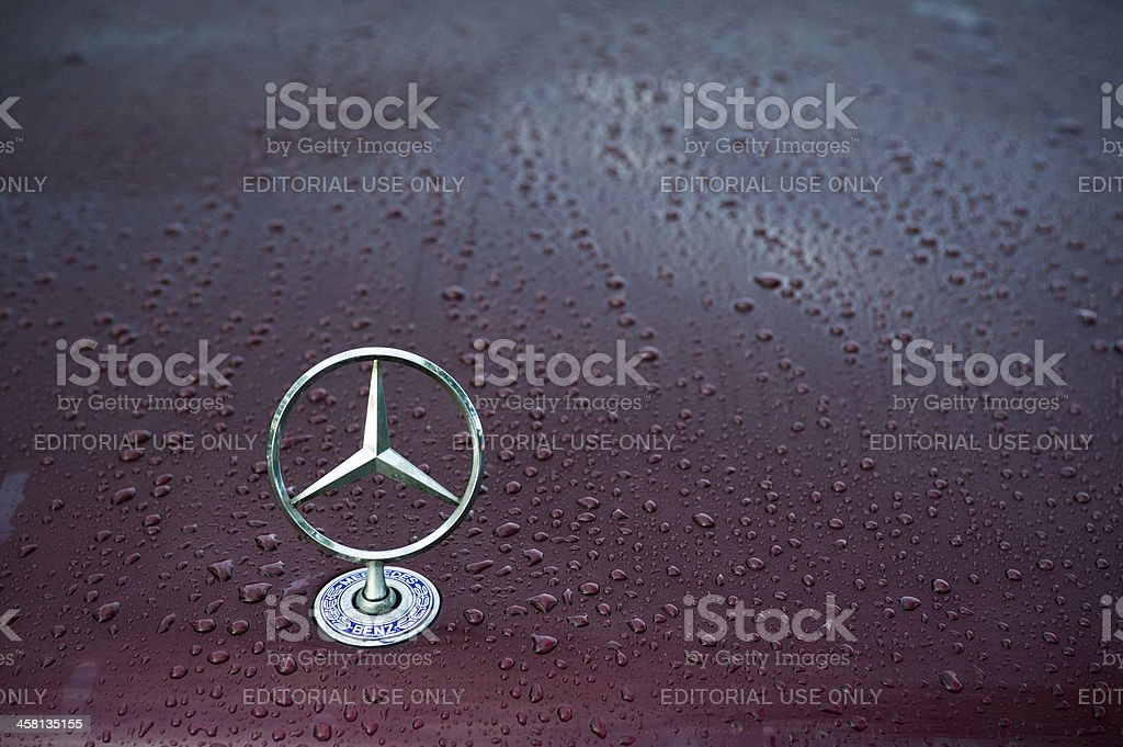 "Mercedes logo ""Padua, Italy - July 6, 2011: Mercedes classical logo on a wet car hood. Mercedes-Benz, a division of Daimler AG, is a German manufacturer of automobiles, buses, coaches, and trucks. The name traces its origins to Daimler 1901 Mercedes and to Karl Benz 1886 Benz Patent Motorwagen, widely regarded as the first automobile. Mercedes today is synonymous with luxury, sportiness and technical reliability. Shot in a public parking."" Automobile Industry Stock Photo"