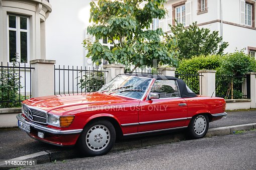 Strasbourg, France - May 19, 2017: Front view of luxury vintage red convertible cabriolet Mercedes-Benz 300 Sl parked in front of French luxury house in calm neighborhood