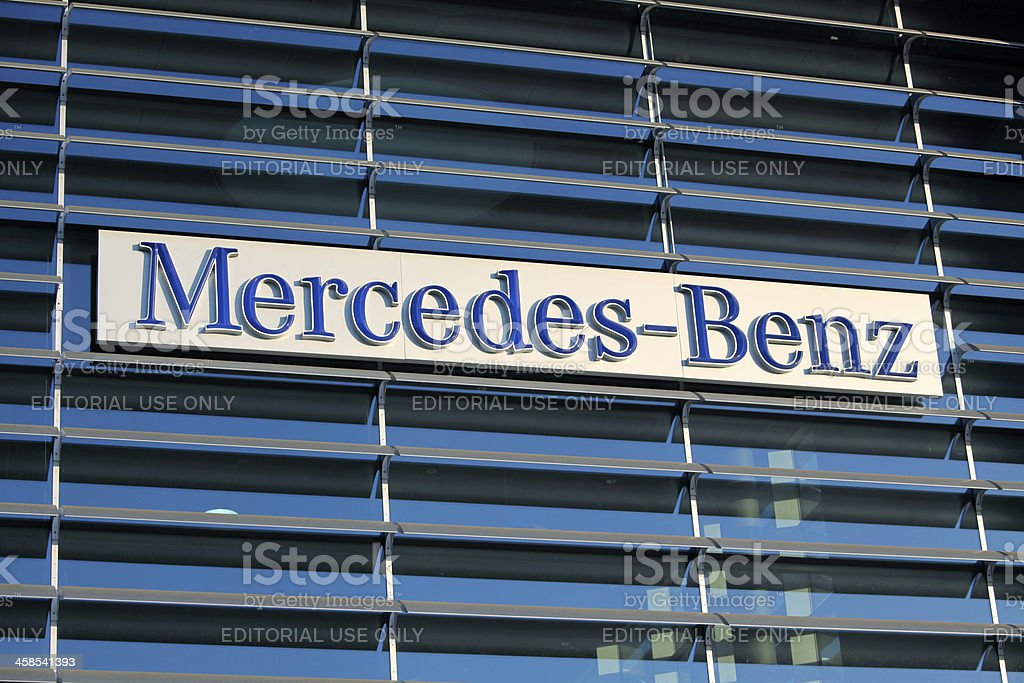 Mercedes-Benz sign at the building facade of a sales store. Photo...