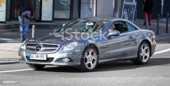 Wiesbaden, Germany - October 30, 2013: A senior man in a silver-metallic Mercedes-Benz SL-Class (R230-series, facelift 2008) drives on a street in the center of Wiesbaden, Germany. In the background a few pedestrians. The SL-Class-cars are 2-door small luxury roadsters with retractable hardtops. Mercedes-Benz is a German manufacturer of automobiles and trucks and a division of Daimler AG, formerly Daimler-Chrysler. Some minor motion blur.