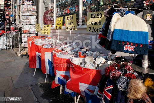 Racks and bins of merchandise outside a souvenir shop in London's West End on a sunny day.
