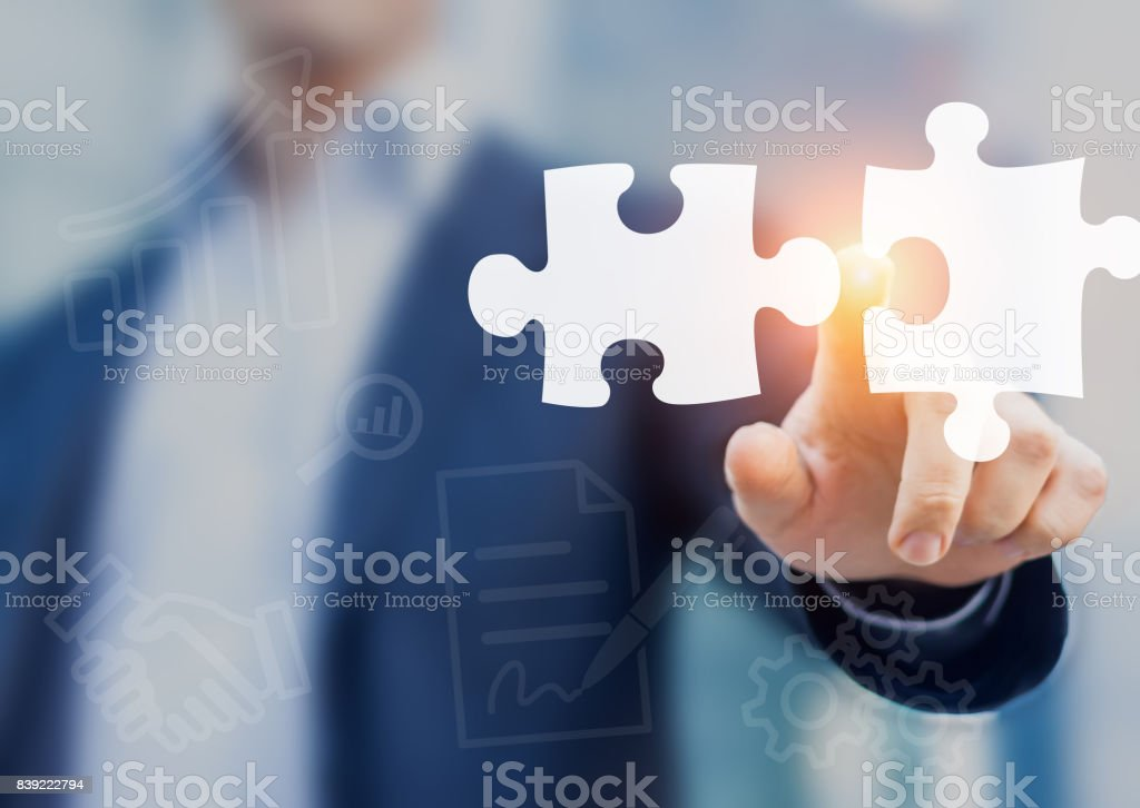 Mergers and acquisition concept with consultant touching puzzle pieces icons stock photo