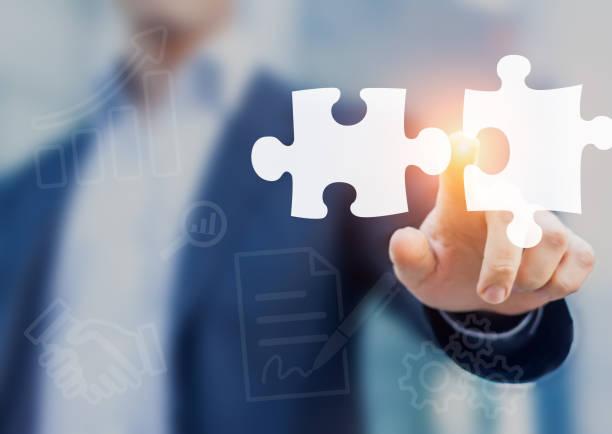 fusionen und erwerb konzept mit berater berühren puzzle-stücke symbole - puzzleteile stock-fotos und bilder