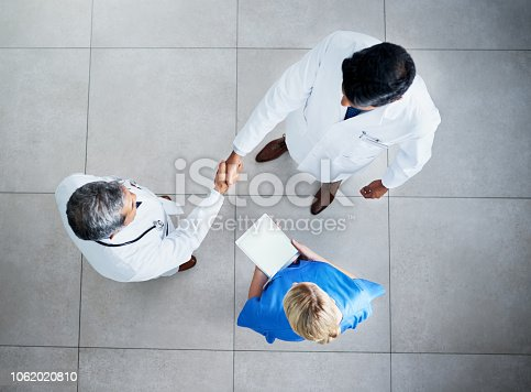Shot of two medical practitioners shaking hands in a hospital