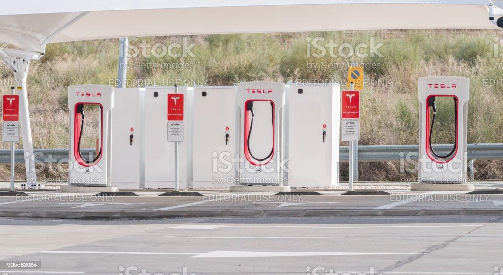 Mérida, Extremadura, España - 12 de enero de 2018: Tesla sobrealimentador estaciones y parking, para coches eléctricos y ecológicos instalado cerca de la autopista A5. Tesla motors desarrolla red de las estaciones de carga en toda Europa y el mundo. - foto de stock