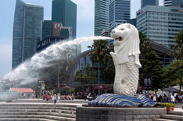 "Merilon Statue, Singapore ""Singapore, Singapore - September 4, 2011: A view to Merilon Statue at Marina Bay in Singapore with tourists and Singapore Skyline in background at day time."" merlion fictional character stock pictures, royalty-free photos & images"