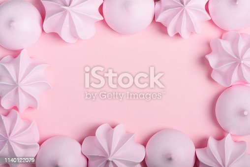 Meringue cookies frame. Sweet crispy twisted and drop meringue border on pink pastel background with copy space.