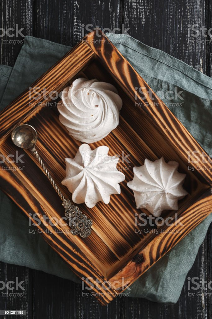 Meringue in a wooden box on a dark background. stock photo